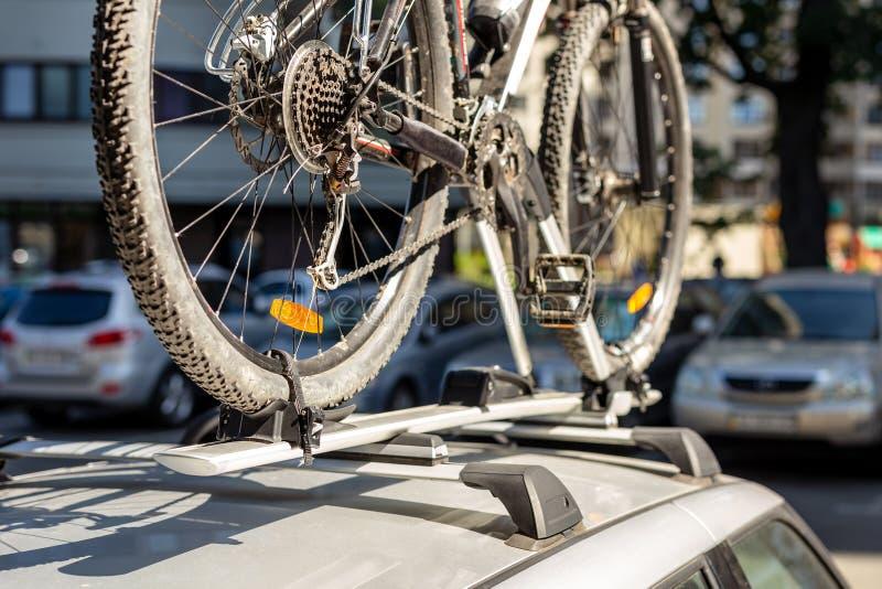 Close-upfiets op het rektraliewerk van het autodak bij openluchtparkeren Voertuig met opgezette fiets op dak Actieve mede sport t stock foto
