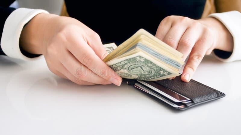 Close-upfoto die van jonge rijke vrouw grote stapel van geld in strakke portefeuille proberen te zetten royalty-vrije stock foto