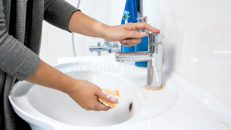 Close-upfoto die van jonge vrouw gele spons met water doorweken alvorens schoonmaakbeurt in badkamers te doen royalty-vrije stock afbeeldingen