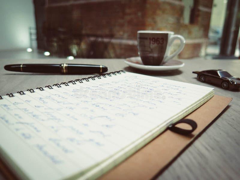 Close-upfoto van Blauw Pen Tinted Spiral Notepad Placed naast de Kop van Pen Die Cast Car en van de Koffie stock afbeeldingen