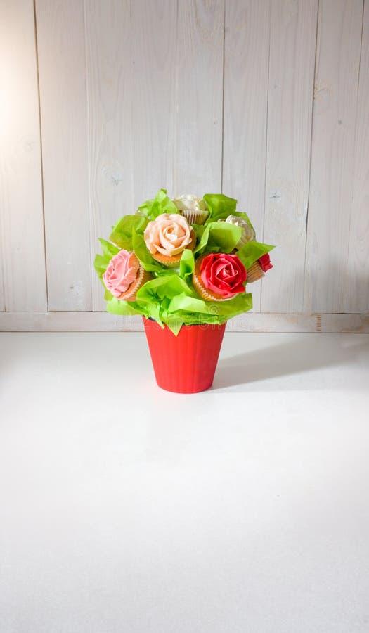 Close-upfoto van bloemboeket van cakes en cupcakes op wit houten bureau wordt gemaakt dat Mooi schot van snoepjes en gebakje royalty-vrije stock afbeelding