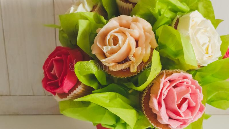 Close-upfoto van bloemboeket van cakes en cupcakes op wit houten bureau wordt gemaakt dat Mooi schot van snoepjes en gebakje stock fotografie