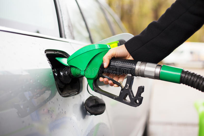 Close-upfoto van de brandstofpomp van de handholding en het opnieuw vullen van auto bij benzinepost royalty-vrije stock foto