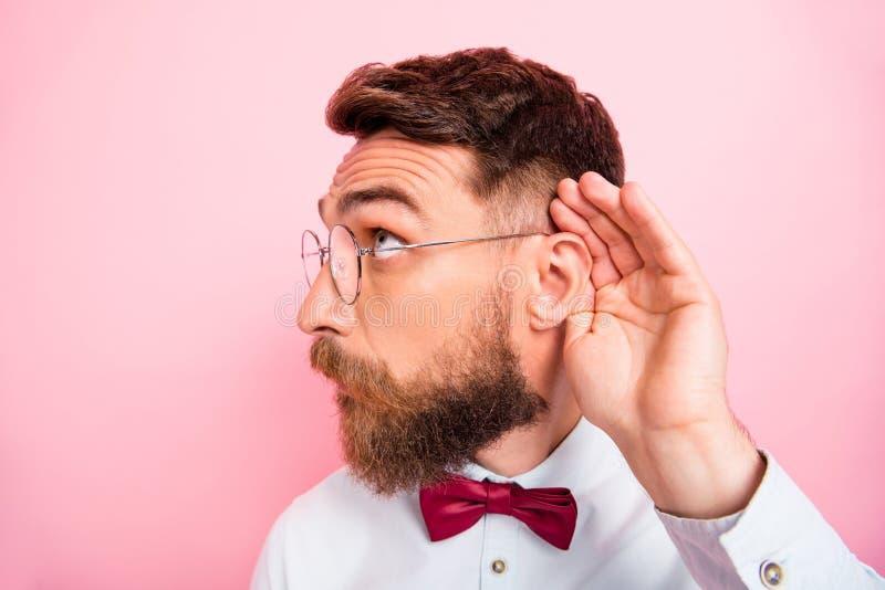 Close-upfoto van de grappige funky slimme geconcentreerde hipster palm van de herenholding dichtbij oor die vertrouwd geluid vang royalty-vrije stock afbeelding