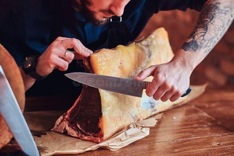 Close-upfoto van een chef-kokkok die exclusief schokkerig vlees op lijst in een keuken met zolderbinnenland snijden royalty-vrije stock afbeelding