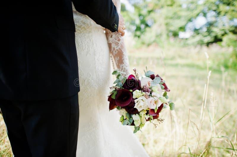 Close-upfoto van een mooi huwelijksboeket in bruid` s handen royalty-vrije stock afbeeldingen