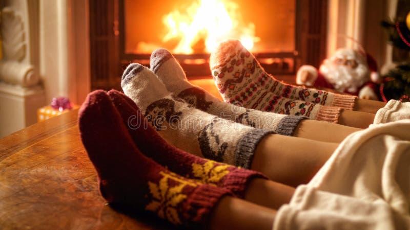 Close-upfoto van familievoeten in wollen sokken die naast open haard liggen royalty-vrije stock foto's