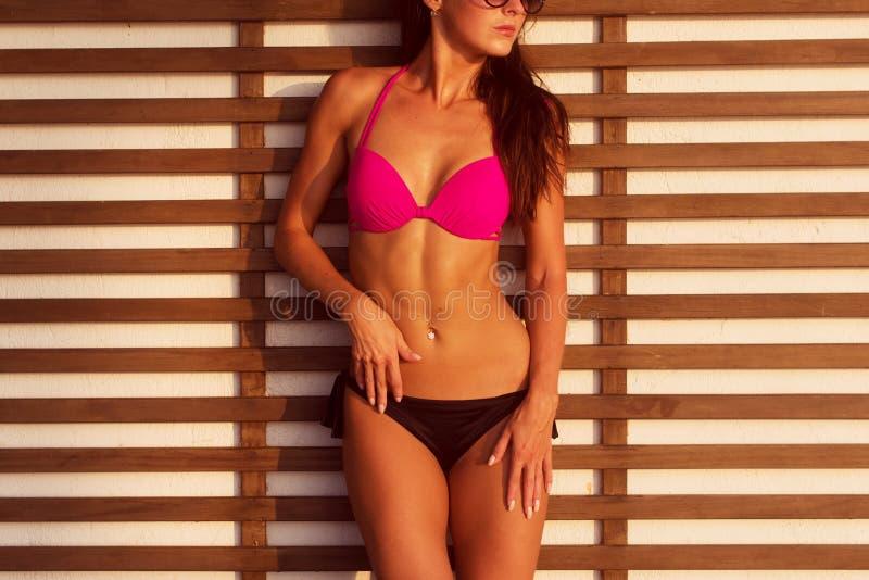 Close-upfoto van gelooid donkerbruin model met sexy lichaam status in bikini en zonnebril tegen muur houten grating  stock foto