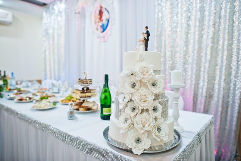 Close-upfoto van grote witte die huwelijkscake met fondantje wordt verfraaid stock foto's