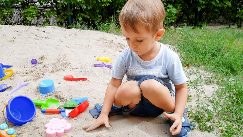 Close-upfoto van 3 jaar het oude peuterjongen spelen met stuk speelgoed in zandbak op speelplaats royalty-vrije stock foto's