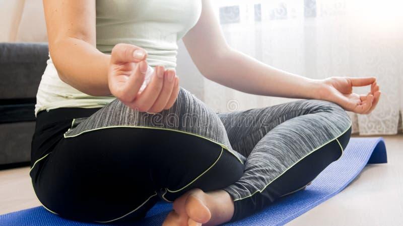 Close-upfoto van jonge vrouw in sportenkleren die thuis mediteren royalty-vrije stock foto