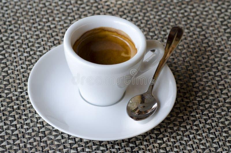 Close-upfoto van koffieespresso in witte porseleinkop op saus stock fotografie