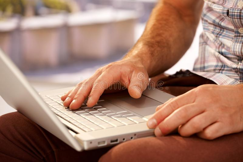 Close-upfoto van mannelijke handen die op laptop typen stock fotografie