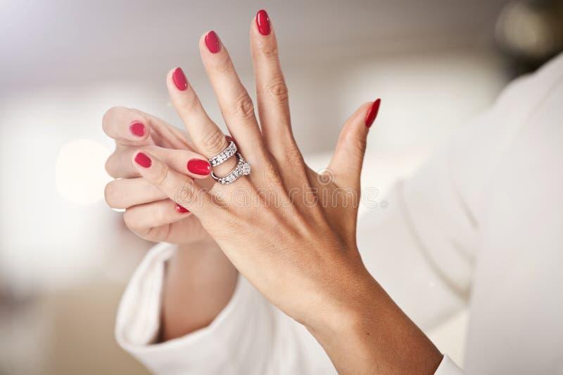 Close-upfoto van mooie vrouwelijke handen met rode spijkers en ele stock foto's