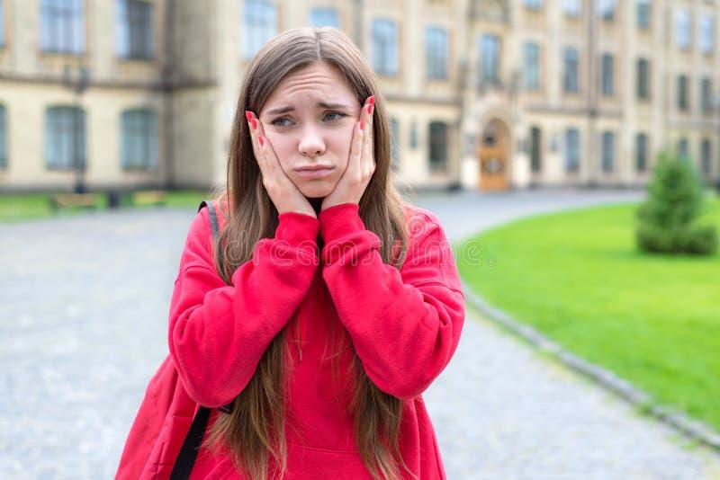 Close-upfoto van nadenkend gelet op peinzend tienermeisje die met grappige gelaatsuitdrukking wat betreft gezicht over slecht tek stock afbeeldingen