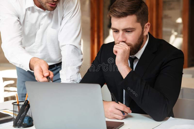 Close-upfoto van twee jonge mensenzitting in bureau en het bespreken stock foto