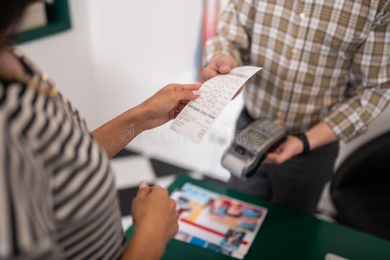 Close-upfoto van verkoper die het ontvangstbewijs overhandigen aan de klant royalty-vrije stock afbeelding
