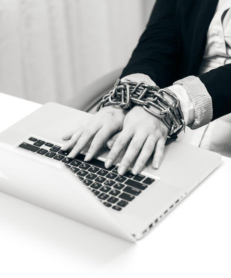 Close-upfoto van vrouw aan laptop door ketting wordt gesloten die stock foto