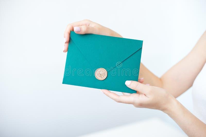 Close-upfoto van vrouwelijke handen die een groene uitnodigingsenvelop met een wasverbinding houden, een giftcertificaat, een pre stock foto's