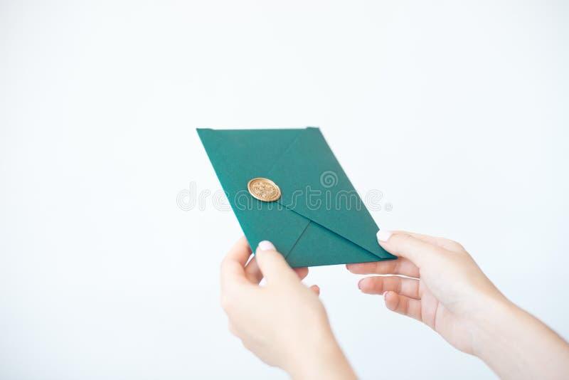 Close-upfoto van vrouwelijke handen die een groene uitnodigingsenvelop met een wasverbinding houden, een giftcertificaat, een pre royalty-vrije stock afbeeldingen