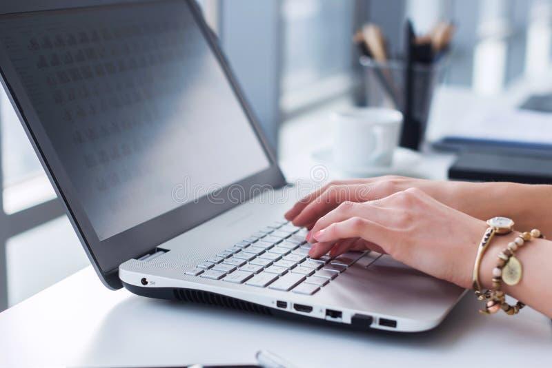 Close-upfoto van vrouwelijke handen met toebehoren die aan draagbare computer in een modern bureau werken, die toetsenbord gebrui royalty-vrije stock afbeeldingen
