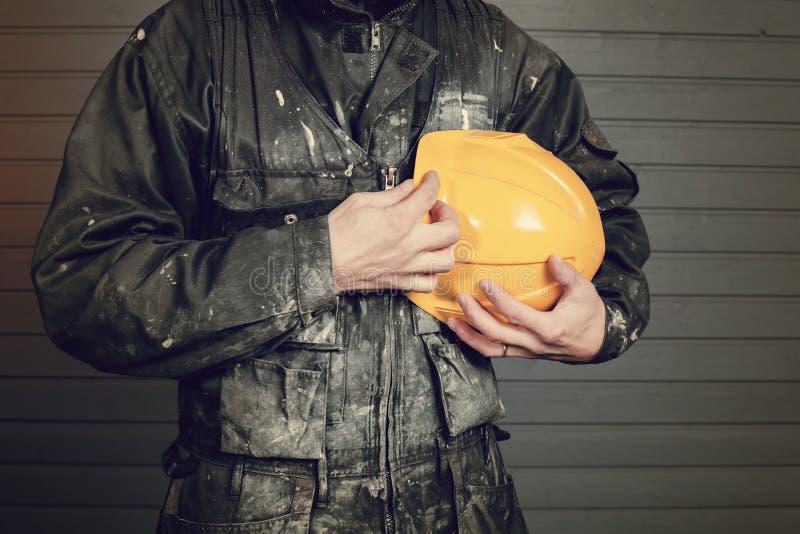 Close-upfoto van vuile laborer& x27; s overall en een gele veiligheidshelm stock afbeelding