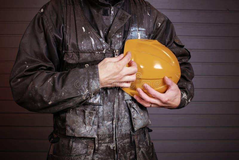 Close-upfoto van vuile laborer& x27; s overall en een gele veiligheidshelm stock foto's