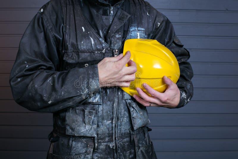Close-upfoto van vuile laborer& x27; s overall en een gele veiligheidshelm stock afbeeldingen