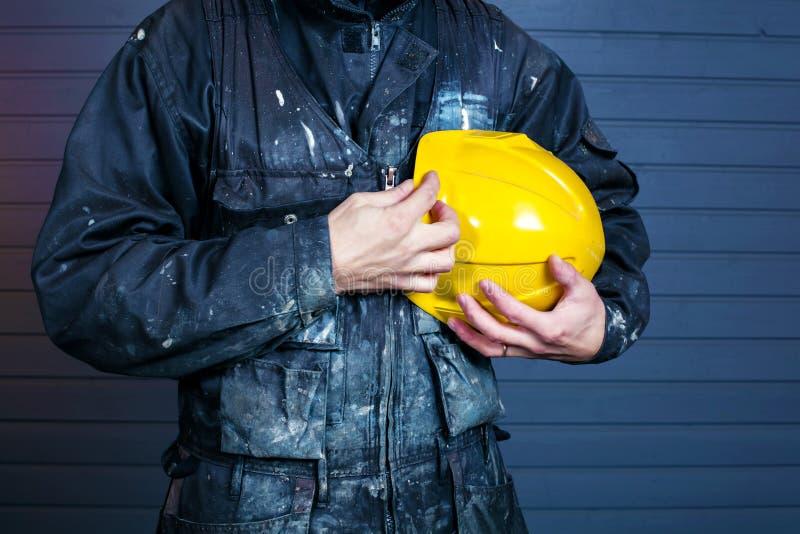 Close-upfoto van vuile laborer& x27; s overall en een gele veiligheidshelm stock fotografie