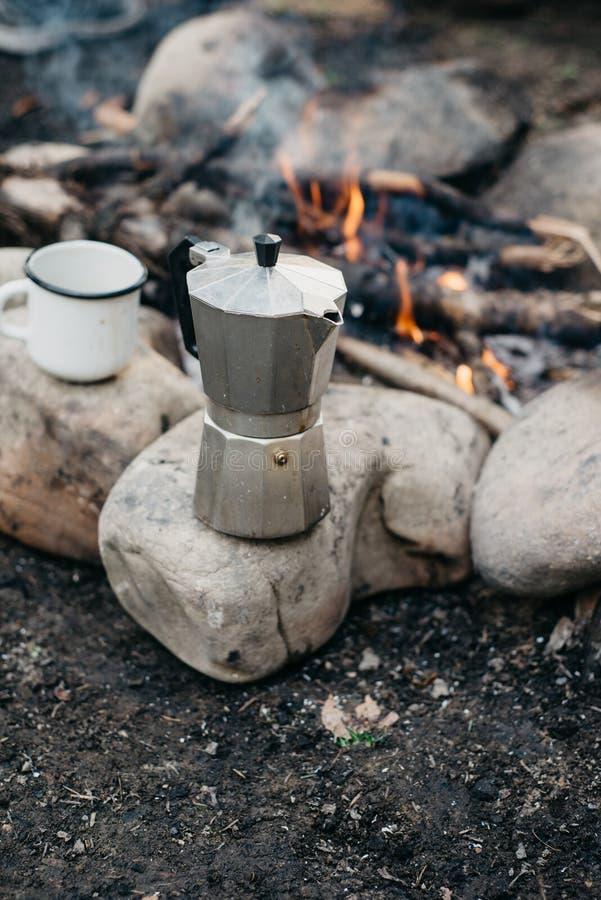 Close-upfoto van wit kop en koffiezetapparaat dichtbij aan vuur De actieve vakanties van het conceptenavontuur openlucht stock foto
