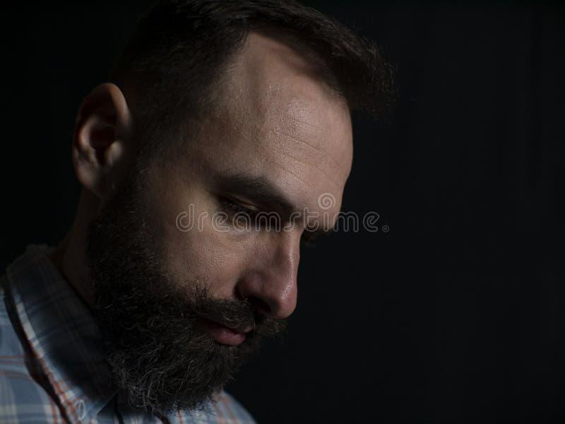 Close-upgezicht van een modieuze mens met een baard en snor met een ernstig gezicht die neer op een zwarte achtergrond kijken royalty-vrije stock afbeelding