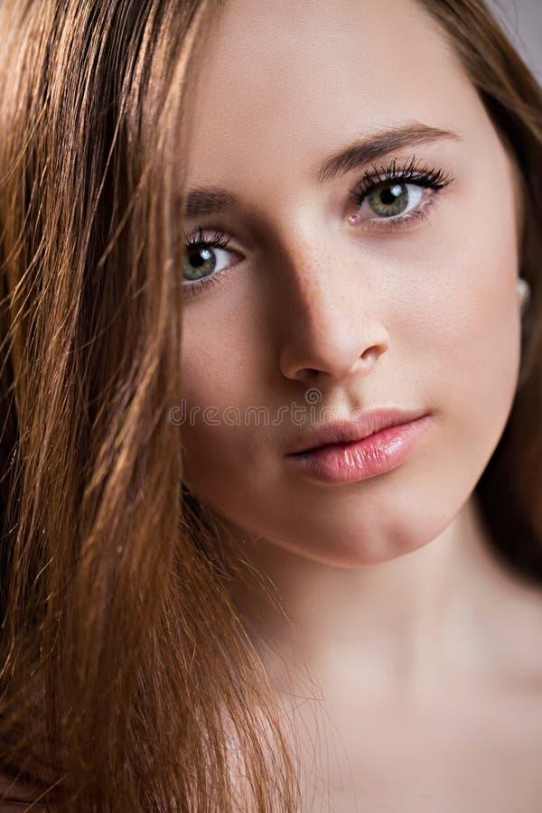 Close-upgezicht van een mooie roodharige jonge vrouw met sproeten Het charmante meisje met schone huid, natuurlijke schoonheid on royalty-vrije stock foto's