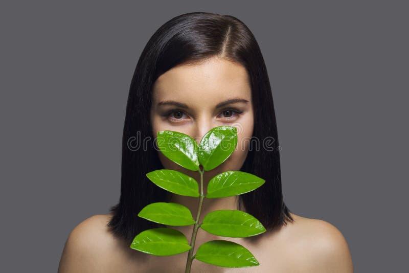 Close-upgezicht van jonge mooie vrouw met groen blad Natuurlijk schoonheidsportret van brunette met perfect gezondheidshuid en ha stock foto