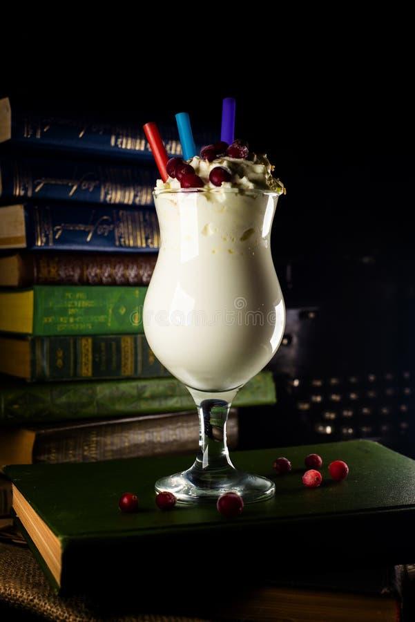 Close-upglas met milkshake, met een stro op achtergrond met boeken royalty-vrije stock afbeelding