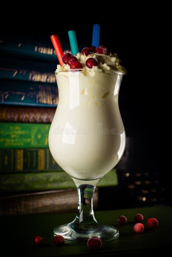 Close-upglas met milkshake, met een stro op achtergrond met boeken stock fotografie