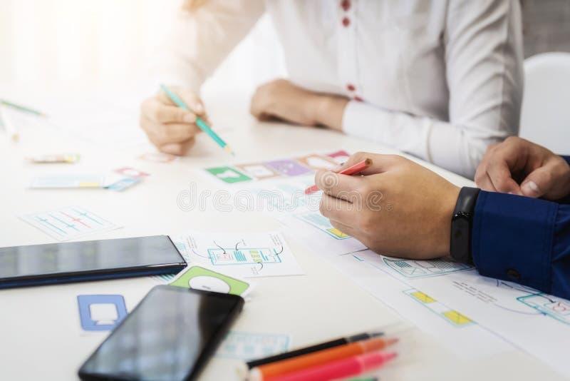 Close-uphand die van grafische ontwerper over het ontwerp van de wireframetoepassing in bureau werken Het concept van de gebruike stock afbeeldingen