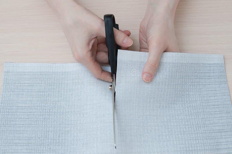 Close-uphanden die doek met schaar snijden stock fotografie