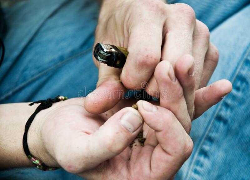 Close-uphanden die van de mens een Marihuanaverbinding rollen stock foto's