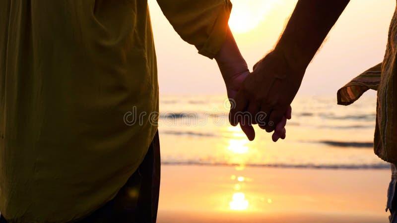 Close-uphanden die van hoger paar zich op het strand bevinden en een zonsondergang bewonderen stock afbeeldingen