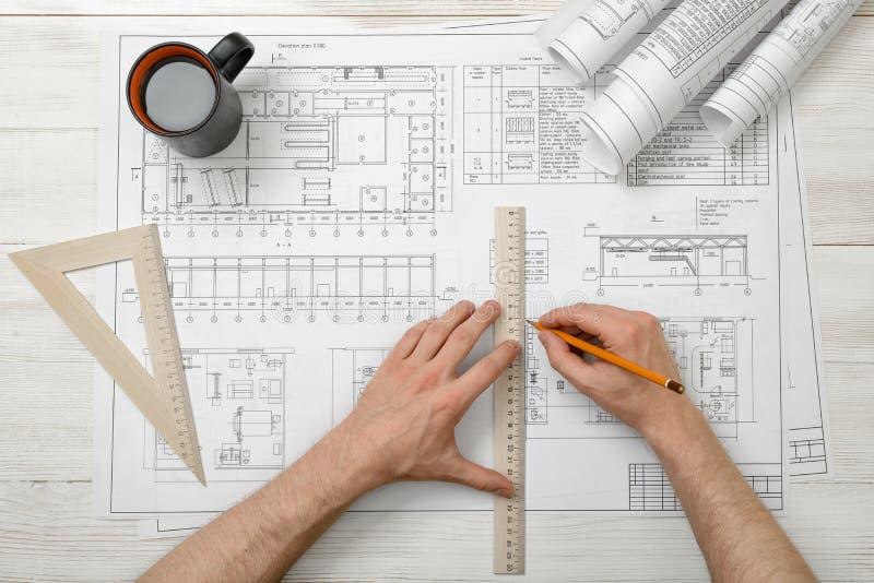 Close-uphanden van architect terwijl het werken van proces met centimeterheerser stock foto