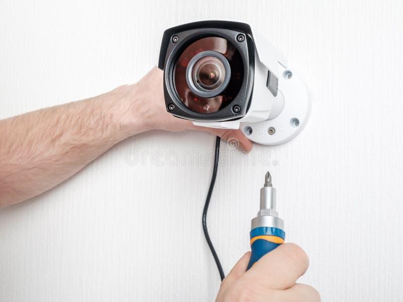 Close-uphanden van technicus die kabeltelevisie-camera aanpassen stock afbeeldingen