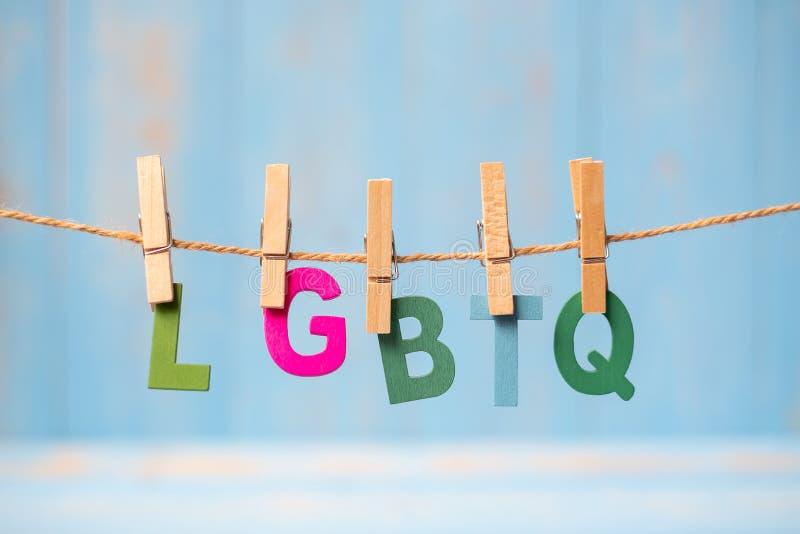 Close-uplgbtq tekst, voor lesbienne, vrolijk, biseksueel, transsexueel, en hangen online met blauwe houten achtergrond stock fotografie