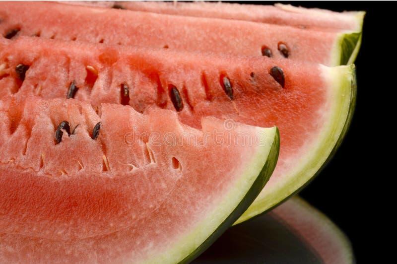 Close-upmacro van plakken van watermeloen op zwarte wordt geschoten die stock afbeelding