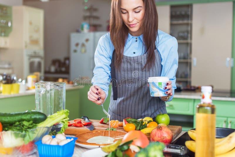 Close-upmening die van vrouwelijke handen condens op cakelaag uitspreiden die zich in keuken bevinden stock afbeelding