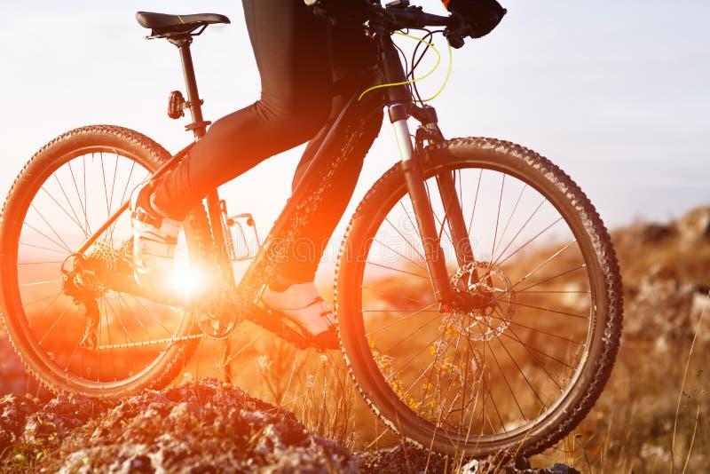 Close-upmening over een fietserfietser die een fiets berijden op de maniermening van onderaan over een achtergrond van zonsopgang stock afbeelding