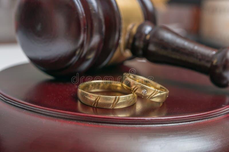 Close-upmening over gouden ringen en hamer op achtergrond Scheidingsconcept stock fotografie