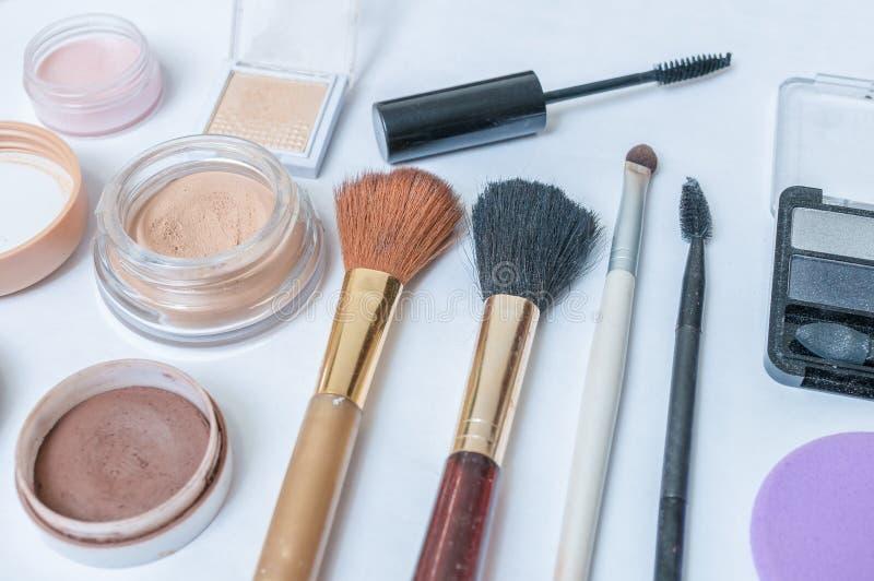 Close-upmening over schoonheidsmiddelen, make-up en borstels op witte achtergrond royalty-vrije stock afbeeldingen