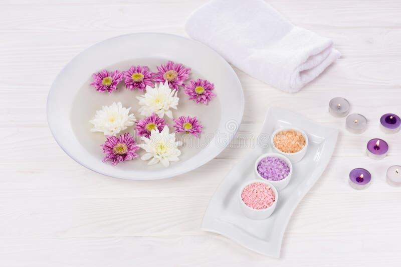 close-upmening van bad voor spijkers met bloemen bij lijst met handdoek, kleurrijke overzeese zout en aromakaarsen voor manicure  royalty-vrije stock afbeeldingen