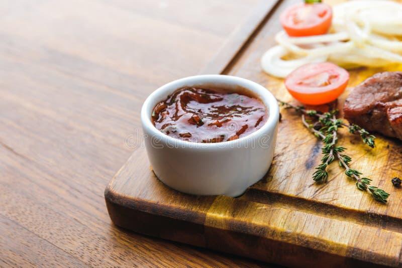 Close-upmening van bbq saus en geroosterd vlees met groenten stock afbeelding