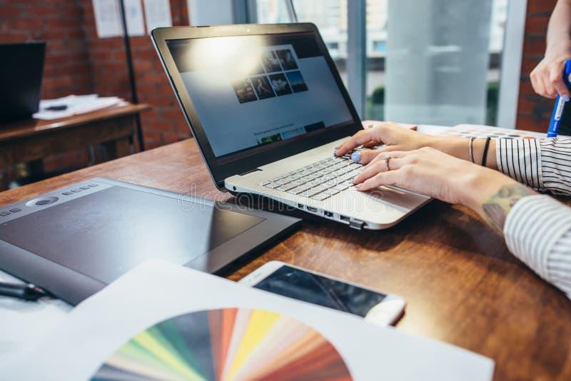 Close-upmening van binnenlandse ontwerperwerkruimte met laptop, grafische tablet, telefoon en kleurenpalet op bureau stock foto